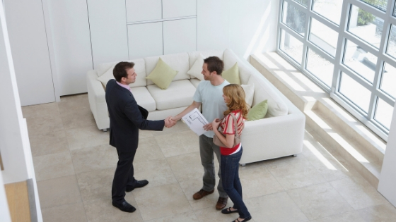 real estate agent with a couple inside a house